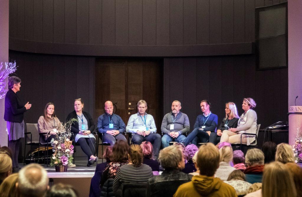 Professor Kari Dyregrov (stående) styrer paneldebatten med etterlatte ved narkotikarelatert død. F.v: Berit Lie, Sølvi Kaald, Trond Einar Michelsen, Ole Jørgen Lygre, Paul Smines, Bjørn Ole Helliksen, Hilde Bergesen og Eva Semmingsen